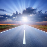 Driving on asphalt road towards the sunbeams Stock Photo
