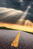 Driving on asphalt road towards the sunbeams Royalty Free Stock Photo