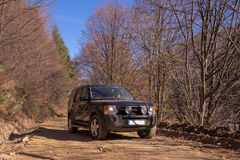Driving in an autumn landscape. Black Land Rover Discovery taken out for offroad driving. Picture taken on a mountain road during autumn Stock Photos