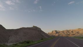 Driving Through Badlands Rock Formations in Morning