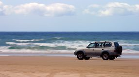 Driving on the beach. Four-wheel-drive SUV moving on a beach with motion blur on the background (Fraser Island, Australia Stock Photography