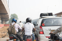 Driving Bikes on Busy Street. Men riding on motorbikes on the streets of Delhi on a busy week day. Cars along with other bike riders are also seen on the Royalty Free Stock Photos
