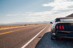 Driving in a black Ford Mustang GT. Through the Death valley in Nevada. Amazing road trip adventure royalty free stock photos