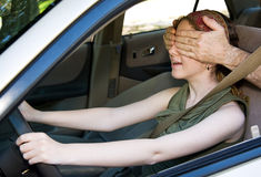 Driving Blind. Teen girl gets the feel of the car while someone covers her eyes royalty free stock photo