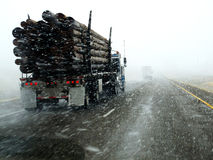 Driving in a Blizzard. Semi truck driving down highway during blizzard snow storm Stock Photos