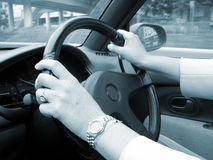 Driving Blues. Shot of a woman with hands on steering wheel, driving, toned in blue Royalty Free Stock Photography