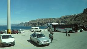 Driving with a bus through the Harbor of Ormos Athinios at Santorini Isle Greece. Bus and ferry terminal passing by. Ormos Athinios, Santorini / GREECE: May 15 stock video footage