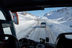 Driving bus in snow storm. Bus journey in blizzard on an alpine road Stock Photo