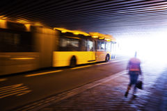 Driving bus under a bridge Stock Photography