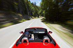 Driving in a cabriolet. Man driving in a red cabriolet fast down the road Royalty Free Stock Photos