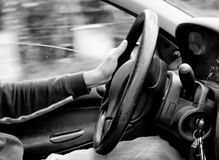 Driving car. Black and white photo of a man driving car royalty free stock image