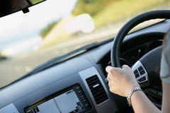 Driving a car. Woman with her hand on the wheel driving a car on a multiple lane highway Stock Images