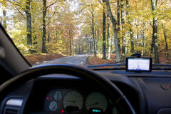 Driving in a car. View from inside a car with road, forest and gps navigator Royalty Free Stock Photo