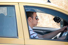 Driving  the car. A young man driving his car and looking good Royalty Free Stock Photography