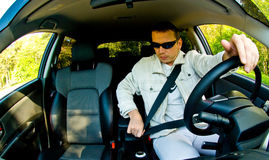 Driving a Car. A fisheye view of a man wearing sunglasses and driving a car Royalty Free Stock Photo