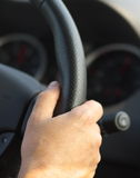 Driving a car. Man's hand on car steering close, black, vertical Royalty Free Stock Photos