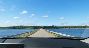 Driving car across the Bridge between lakes. Beautiful road between lake water. Driving car across the Bridge between lakes.  Beautiful road between lake water Stock Images