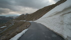 Driving a car along the mountain road in the autumn cloudy evening outdoors on the left valley, a dense tamped snow on. The right. A modern car is slowly moving stock footage
