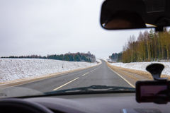 Driving a car on asphalt road in winter Stock Photos