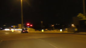 Driving car in the city at night. Driver view when driving in the city at night, passing emergency vans with orange lights flashing and making left turn at stock video footage