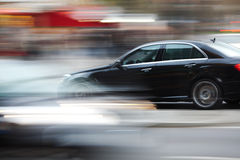 Driving car in city traffic. The photo was taken by panning the camera, so the traffic is shown in motion blur Stock Photos