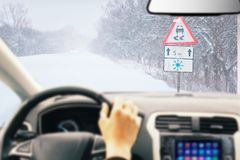 Driving a car - first person shoot. Hands on steering wheel in leather gloves in luxury car driving on a winter ice road stock images