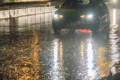 Driving car through the heavy rain in the evening. Traffic under heavy rain with hail in dangerous situation with low visibility, royalty free stock photos