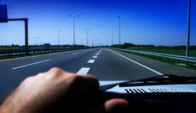 Driving car on highway. Closeup of steering wheel and a hand of a man in a car Royalty Free Stock Photography