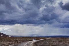 Driving car in Iceland road. Dramatic landscape from Iceland, car on the remote road, wilderness and moody sky Stock Images