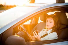 Driving car and looking in phone Stock Image