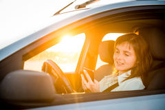 Driving car and looking in phone Royalty Free Stock Images