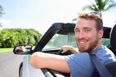 Driving car man happy on road trip travel holidays. Portrait of a young adult smiling at camera ready for his vacations with his new convertible purchase or Stock Photos