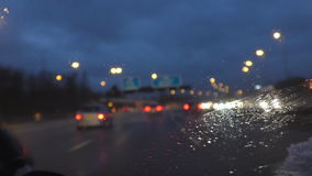 Driving car on motorway at night. Blurred driver view of motorway and transport driving in a rain, focus on wet windscreen stock footage