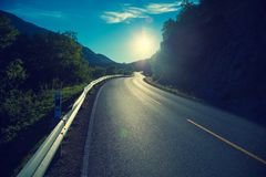 Driving a car on a mountain road at sunset Royalty Free Stock Photo