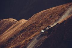 Driving car on mountain unpaved road. White lorry truck on road. Highland landscape. Transportation industry. Cargo traffic. Carri Royalty Free Stock Photos