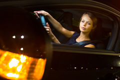 Driving a car at night - pretty, young woman driving her car Stock Images