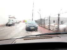 Driving a car in the rain front window. With windscreen wiper Royalty Free Stock Photo