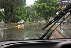 Driving the car in the rain. View of the road through the wet windshield Stock Photo