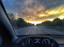 Driving a car at the rainy sunset Royalty Free Stock Photos