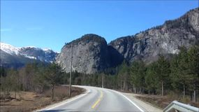 Driving on the Road. Driving a car on a road in Norway, where there are mountains and forest stock video