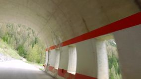 Driving a car on the serpentine through the tunnel to Santa Lucia in the Dolomites stock video footage
