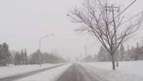 Driving car on slippery roads during cold winter snow storm. Looking out front window of car driving along snow covered road in snowstorm stock footage