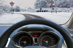 Driving a car in the snow. Car drivers view through the vehicle windscreen whilst driving on a snow covered road approaching a roundabout with Give Way signs royalty free stock photo