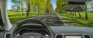 Driving car, steering wheel, travel background. Spring road Royalty Free Stock Image
