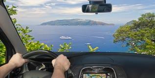 Driving a car towards Sorrento Peninsula, Italy. Driving a car towards the beautiful Sorrento Peninsula, seen from Capri, Bay of Naples, Italy stock images