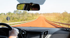 Driving a car into a unpaved dirt road Stock Images