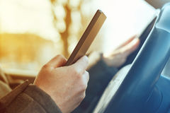 Driving car and using mobile phone to send text message Royalty Free Stock Photo