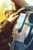 Driving car and using mobile phone to send text message Stock Image