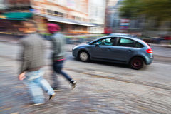 Driving car and walking couple in the city Royalty Free Stock Photography