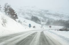 Driving a car on the white and snowy road with a strong wind. Winter weather scene and blizzard. Winter storm. Cars on dangerous. Frozen and icy road on a stock images